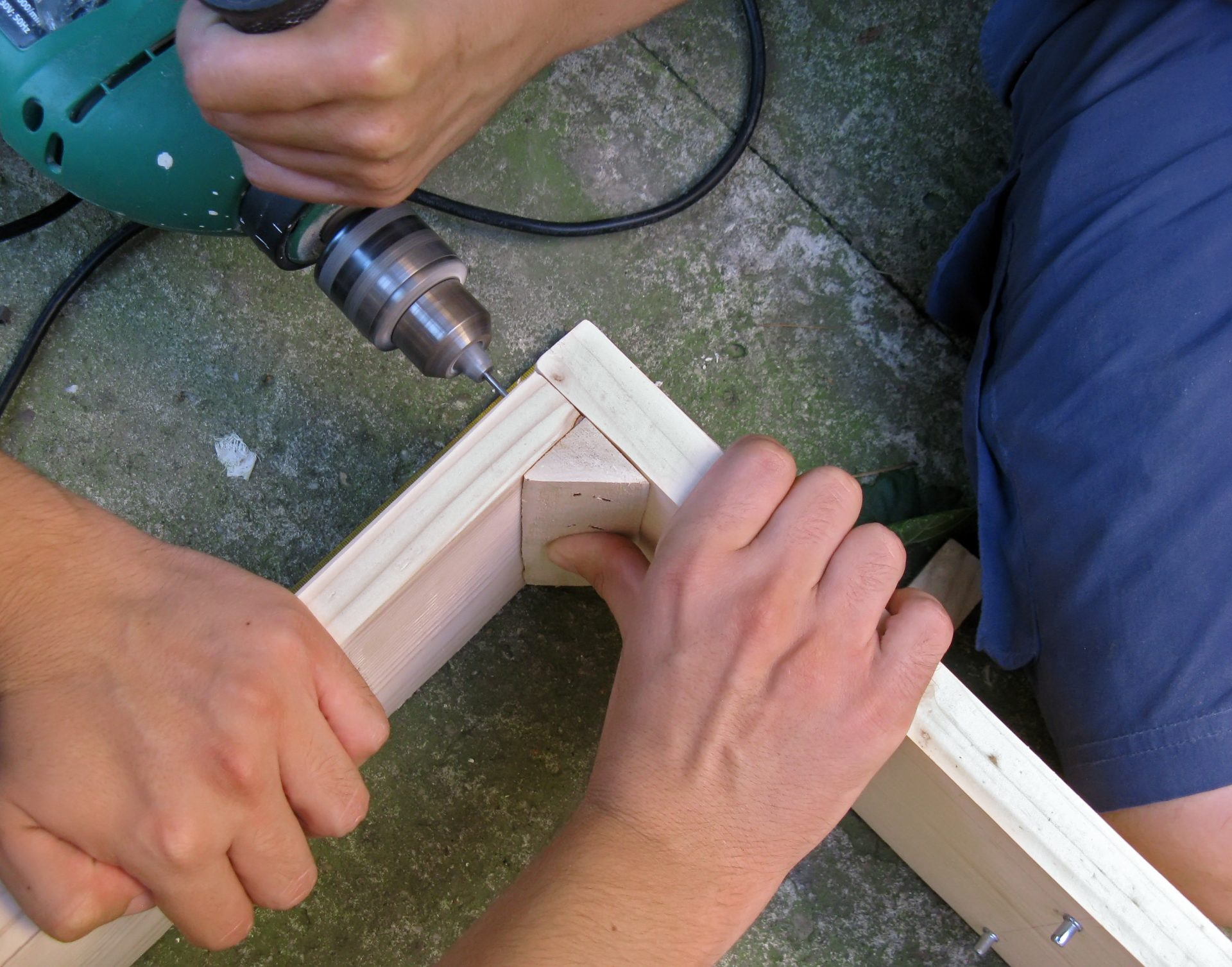 Teamwork - working on building a cabinet. Drilling a hole in wood.