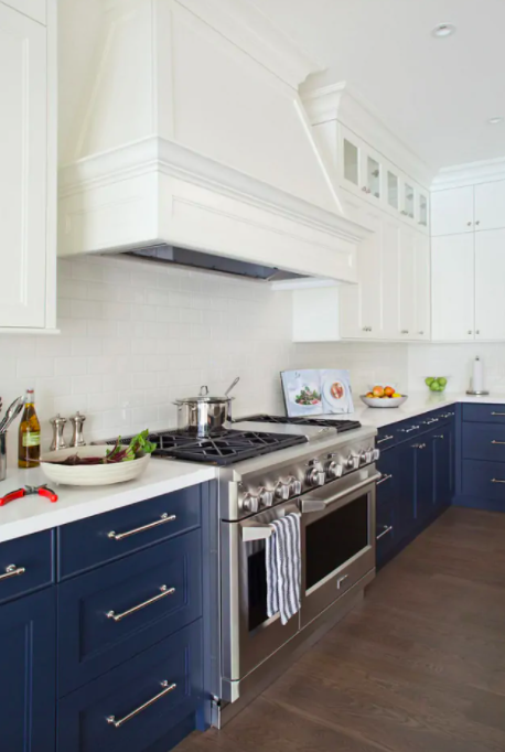 White Shaker-style upper wall cabinets with navy base cabinets